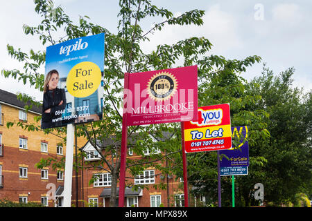 Property for sale and to let signs from a variety of estate agents outside a block of modern apartments, Hatherton Court, Worsely Road North, Walkden, - Stock Photo