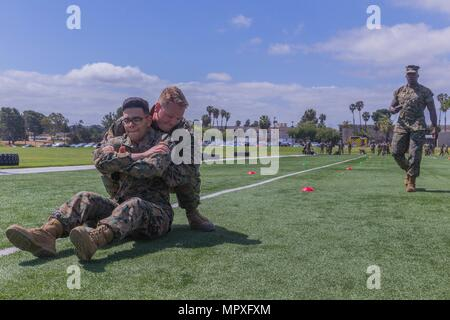 U.S. Marines participates in the buddy drag portion of the maneuver under fire during a combat fitness test for the commanding general's inspection program at Page Field House on Marine Corps Base Camp Pendleton, Calif. May 15, 2018, May 15, 2018. A Marine's physical fitness is essential to the day-to-day effectiveness and combat readiness of the Marine Corps. The Marine Corps considers physical fitness an indispensable aspect of leadership. (U.S. Marine Corps photo by Lance Cpl. Kerstin Roberts/Released). () - Stock Photo