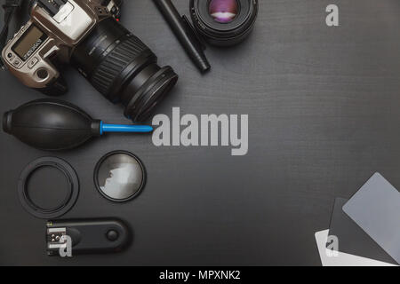 top view of work space photographer with dslr camera system, camera cleaning kit and camera accessory on black table background with copy space - Stock Photo