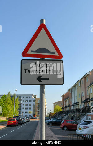 Road sign warning drivers of speed bumps in a residential street. The sign is bilingual with Welsh language translation - Stock Photo
