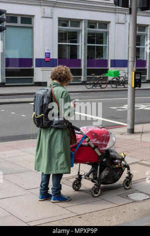a woman pushing a pushchair with a child whilst using a mobile phone at side of the street carrying a rucksack and texting. mum and child. mothering. - Stock Photo
