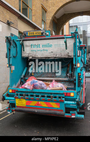 a dust cart lorry or refuse collection services dustbin men in central london. Bin and garbage collection rounds by road. Recycling rubbish landfill. - Stock Photo