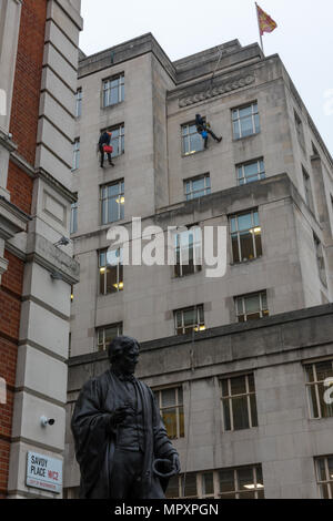 window cleaners abseiling down the side of a tall multi-story office block or building in savoy place wc2 in central london. cleaning windows high up. - Stock Photo
