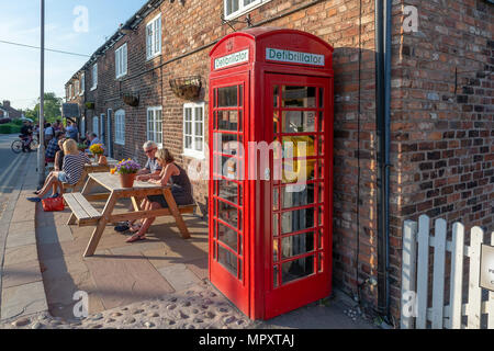 Red K2 telephone box used as a library and defibrillator station outside The Hatton Arms public house in Hatton, Cheshire, England, UK - Stock Photo