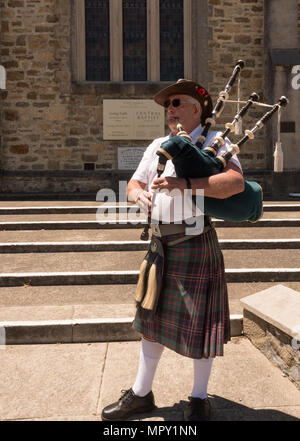 A bagpiper playing a tune outside a church in Albany, Australia - Stock Photo