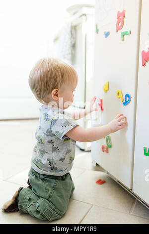 Side view of baby boy playing with colorful magnetic letters and numbers on metallic cabinet at home - Stock Photo