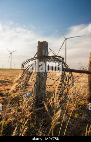 Barbed wire on wooden fence against windmills and cloudy sky at farm - Stock Photo