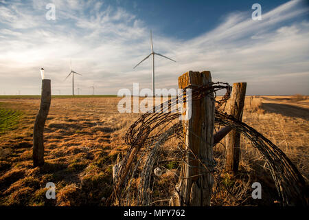Barbed wire on wooden fence against wind turbines and cloudy sky - Stock Photo