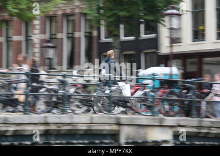 A man rides his bicycle across a canal in Amsterdam, the Netherlands. - Stock Photo