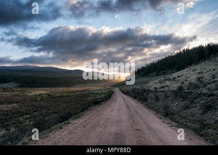 Empty dirt road amidst landscape against cloudy sky during sunset - Stock Photo