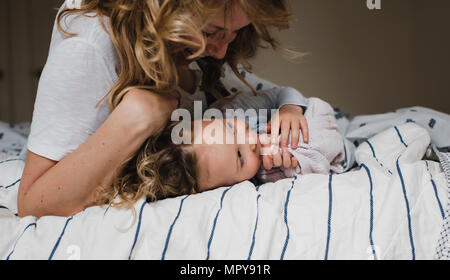 Happy mother playing with daughter while lying on bed at home - Stock Photo