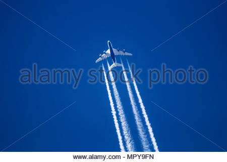 Low angle view of jet plane flying against clear blue sky - Stock Photo