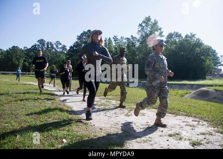 Family members of 3rd Infantry Division Headquarters and Headquarters Battalion Soldiers run to the finish line of the Marne Mile Obstacle Course during the battalion's Spouse's Day event April 20, 2017 at Fort Stewart, Georgia. In addition to the Marne Mile, they also fired M4 carbines at the EST 2000 and a live range. (U.S. Army photo by Staff Sgt. Candace Mundt/Released) - Stock Photo