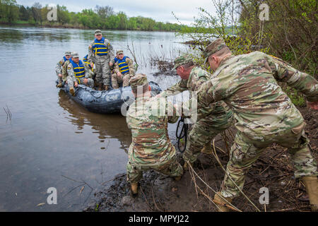 U.S. Army National Guard Soldiers and noncommissioned officers from the six New England states, New Jersey, and New York receive assistance in landing at Washington Crossing State Park, Titusville, N.J., after crossing the Delaware River in a combat rubber raiding craft during the Region 1 Competition Best Warrior Competition April 26, 2017. The Guardsmen reenacted Gen. George Washington's crossing of the Delaware River, which occurred on the night of December 25–26, 1776, during the American Revolution, and was part of a surprise attack against the Hessian forces in Trenton, N.J., on Dec. 26, - Stock Photo