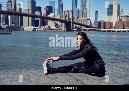 Black Woman Stretches Before Running in New York City - Stock Photo