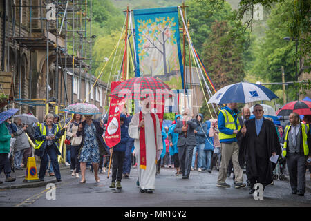 Delph, UK. 25th May 2018. Ministers head the procession along the High Street during the annual 'Whit Walks' through the village of Delph in the district of Saddleworth, Greater Manchester. Credit: Matthew Wilkinson/Alamy Live News - Stock Photo