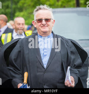 Delph, UK. 25th May 2018. A ministers heads the procession along the High Street during the annual 'Whit Walks' through the village of Delph in the district of Saddleworth, Greater Manchester. Credit: Matthew Wilkinson/Alamy Live News - Stock Photo