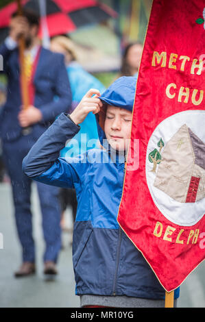 Delph, UK. 25th May 2018. A young banner holder struggles with the rain as he walks along the procession during the annual 'Whit Walks' through the village of Delph in the district of Saddleworth, Greater Manchester. Credit: Matthew Wilkinson/Alamy Live News - Stock Photo