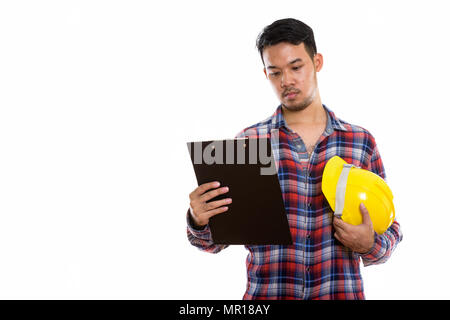Studio shot of young Asian man construction worker reading on cl - Stock Photo