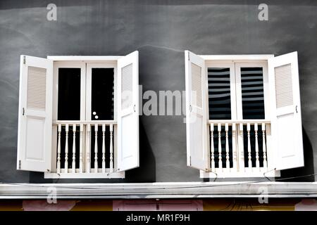 Traditional vintage Singapore shop house with antique white shutters and gray exterior in historic Chinatown - Stock Photo