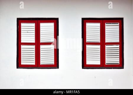 Front view of vintage wooden shuttered windows on the white exterior of an old Singapore shophouse in historic Chinatown - Stock Photo