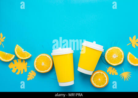Paper cups with lemon slices and tropical leaves on a bright blue background. Summer drink to go flat lay with copy space. Lemonade from above - Stock Photo