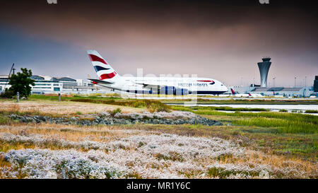 world's largest passenger aircraft,taxis to takeoff position,at San Francisco international airport,seen from across marshland against dramatic sky, - Stock Photo