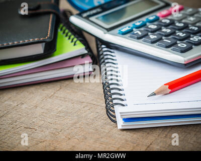 Office accessories including note book, red pencil and calculator on wooden background. Education and business concept. - Stock Photo