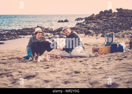 nice beautiful couple of male and female do a pic nic on the beach near thw wave with a dog border collie. love and friendship concept in summer vacat - Stock Photo