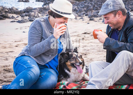 beautiful middle age couple in leisure on the beach in vacation summer time with a cute pet border collie. all together with a cup of coffee to anejoy - Stock Photo