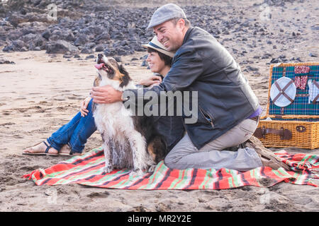freedom and leisure pic nic activity on the beach for an alternative family group of friends two person and a nice dog. everybody have fun outdoor in  - Stock Photo