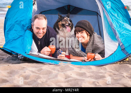 family portrait for alternative vacation time summer on the beach with a tent. nice and smile a male and a woman with a border collie dog in the middl - Stock Photo