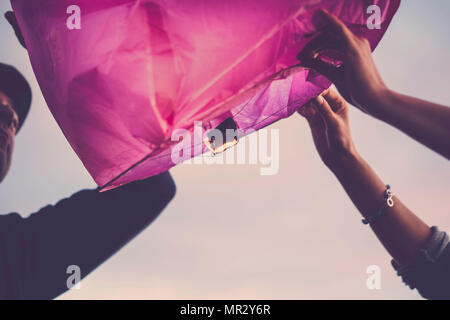 pink chinese lantern ready to fly to realize dreams for a nice couple of man and woman together forever - Stock Photo