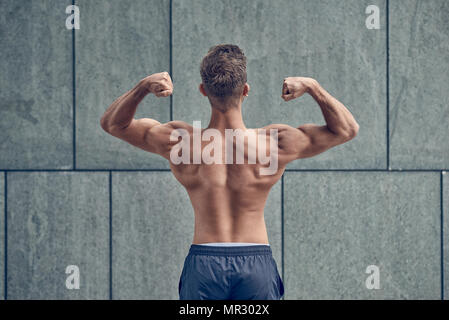 Young male bodybuilder posing with his back to the camera - Stock Photo