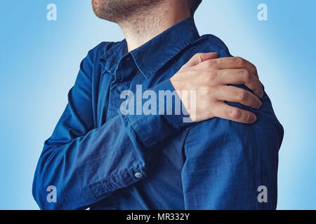 Businessman holding his hand to his aching back. A young guy in a blue shirt complains of pain in his shoulder. fracture of the forearm. concept of he - Stock Photo