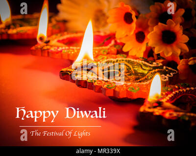 Colorful clay diya lamps lit with flowers for the Hindu Diwali festival. - Stock Photo