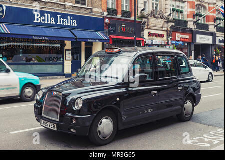 London, UK - April 2018: London taxi cab driven on Shaftesbury Avenue, a major street in the West End of London near Piccadilly Circus - Stock Photo