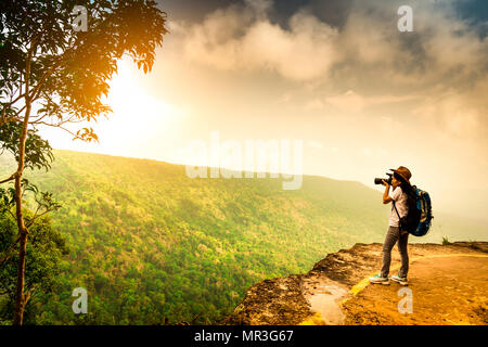 Young traveling woman with backpack, hat and camera stand on the mountain cliff. Female photographer taking picture of tropical forest, sky and clouds - Stock Photo