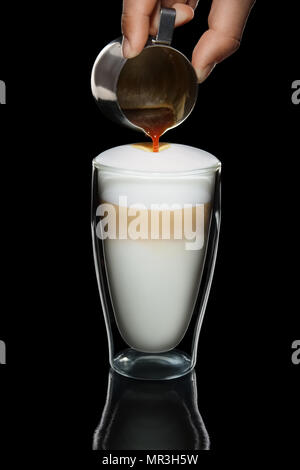 Hand with pitcher making pattern on cappiccino topping - Stock Photo