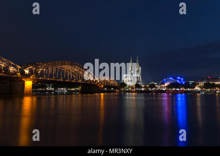 Cologne, Germany - May 23, 2018: Hohenzollern Bridge, Cologne Cathedral and Musical Dome at dusk - Stock Photo