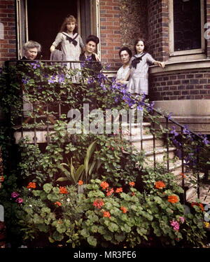 family posing on the steps of their home, France 1908. photographed in Autochrome Lumière, an early colour photography process. Patented in 1903 by the Lumière brothers in France and first marketed in 1907, it was the principal colour photography process in use before the advent of subtractive colour film in the mid-1930s - Stock Photo