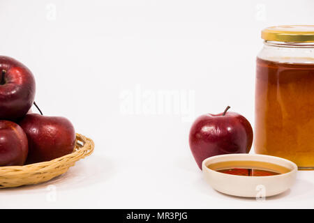 Pile of apples and red apple and jar of honey bowl of honey isolated on a white background. Symbols of Jewish New Year - Rosh Hashanah. - Stock Photo