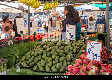 Image of fresh Avocados and other fruits seen on display at an open air market in England. - Stock Photo