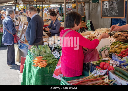 Asian woman seen paying for fresh produce at an open air market in an English city centre. - Stock Photo