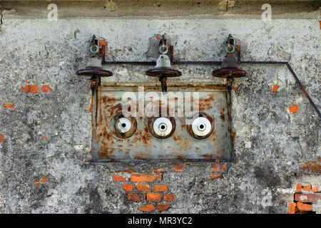 Old, rusty electric power line and fuses on an old, ruined brick wall - Stock Photo