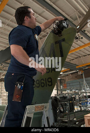 Thomas Martinez, 54th Helicopter Squadron aircraft mechanic, prepares to drain oil from a gear box at Minot Air Force Base, N.D., May 2, 2017. Squadron members also engage in emergency search and rescue mission training. (U.S. Air Force photo/Airman 1st Class Jonathan McElderry) - Stock Photo
