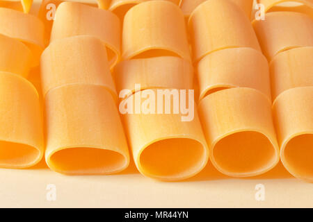 Lines of paccheri pasta on a light yellow background ,in evidence irregular pasta shapes ,horizontal composition - Stock Photo