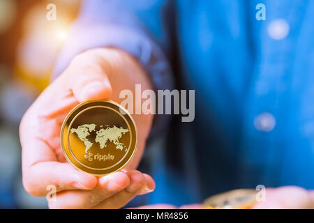 cryptocurrency coins - Ethereum, Litecoin, Bitcoin, Ripple. Women hold the cryptocurrency coin on hand. Physical bitcoins gold and silver coins - Stock Photo