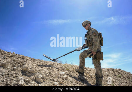 Staff Sgt. Kyle Osgood, 99th Civil Engineer Squadron explosive ordnance disposal technician, uses a metal detector to clear a perimeter during training exercises on Nellis Air Force Base, Nev., May 3, 2017. EOD technicians detect, identify, recover, disarm and dispose of unsafe explosives and ordnance. (U.S. Air Force photo by Senior Airman Kevin Tanenbaum/Released) - Stock Photo