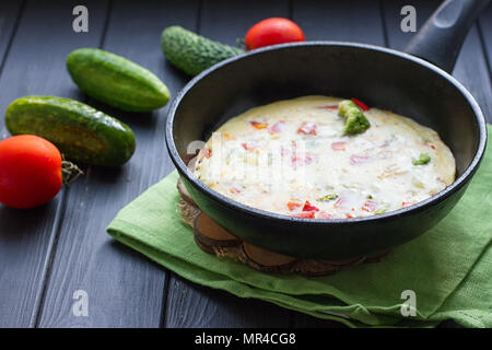 Breakfast set. Pan of fried eggs with fresh tomato, cucumber, sage on dark serving board over black background - Stock Photo